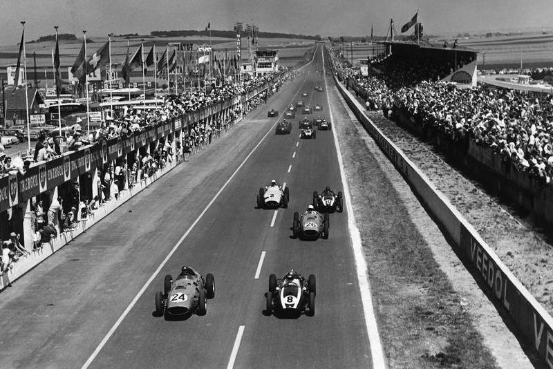 Tony Brooks, #24 Ferrari Dino 246 and Jack Brabham in a Cooper T51-Climax lead at the start.
