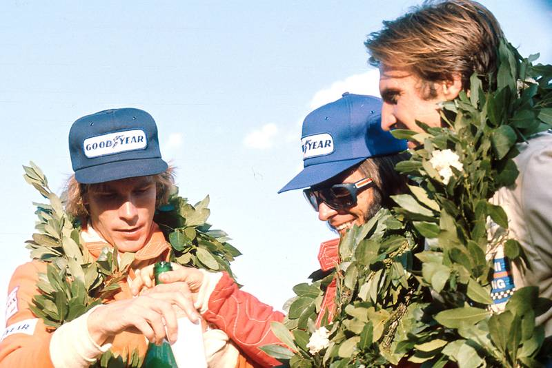 Emerson Fittipaldi is flanked by James Hunt (left) and Carlos Reutemann (right) on the podium.