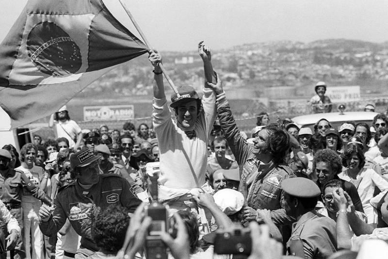 Carlos Pace (Brabham) raises the Brazilian flag aloft as he celebrates winning the 1975 Brazilian Grand Prix.