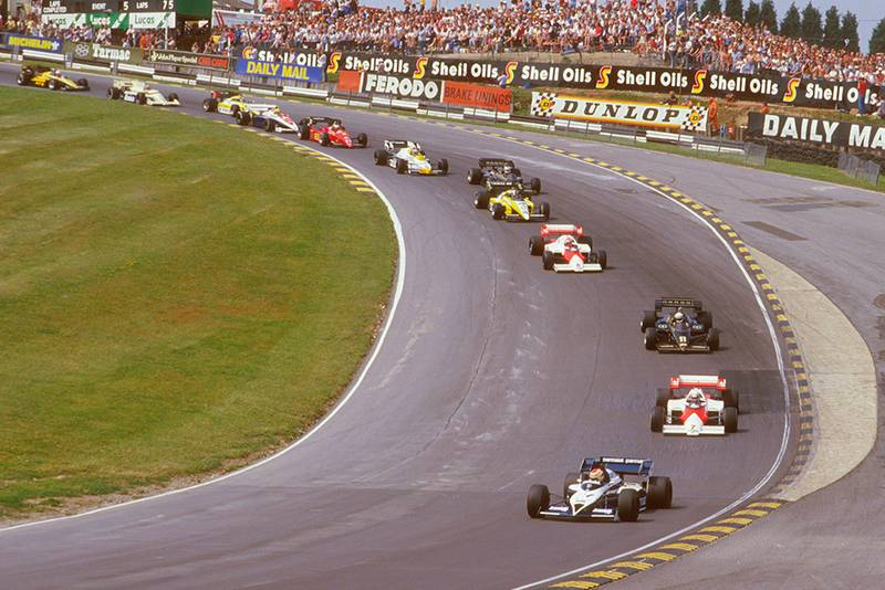 Nelson Piquet (Brabham BT53 BMW) leads Alain Prost (McLaren MP42 TAG Porsche), Elio de Angelis (Lotus 95T Renault), Niki Lauda (McLaren MP42 TAG Porsche), Derek Warwick (Renault RE50) and Nigel Mansell (Lotus 95T Renault) at the start through Paddock Hill Bend.