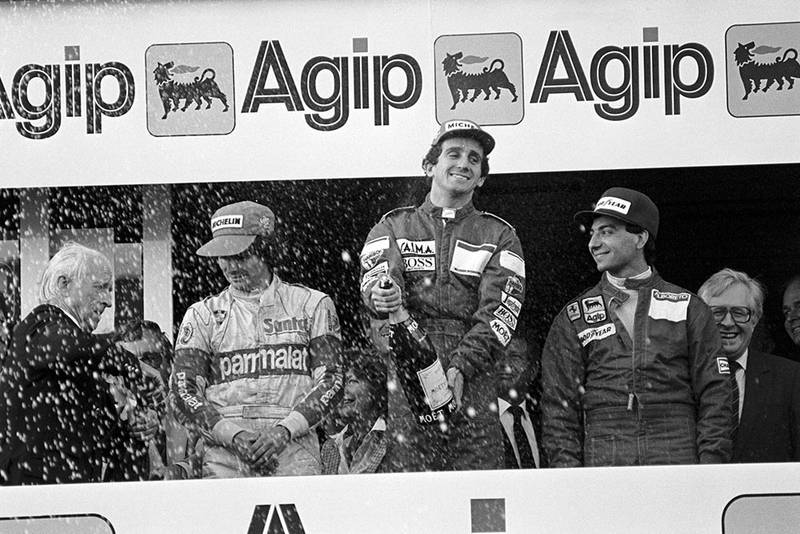 Nelson Piquet (left) third; Alain Prost (centre) first; Michele Alboreto (right) second on the podium.