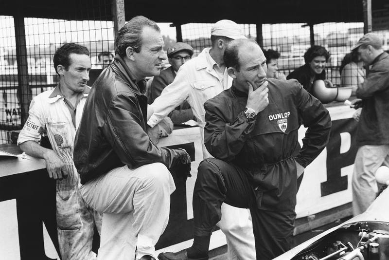 Stirling Moss and Harry Schell chat in the pits.