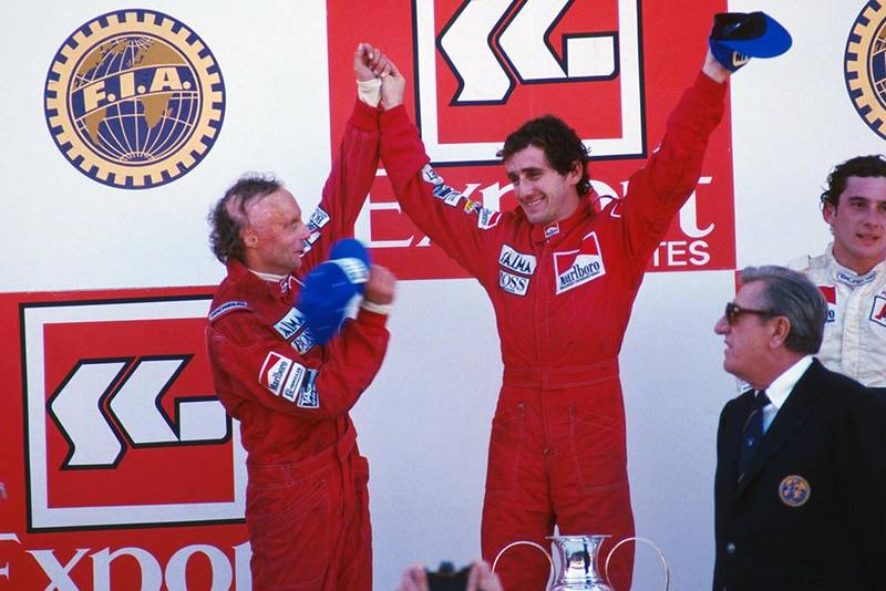 Alain Prost, 1st, (centre) with second place Niki Lauda, left, and third place Ayrton Senna, right on the podium.