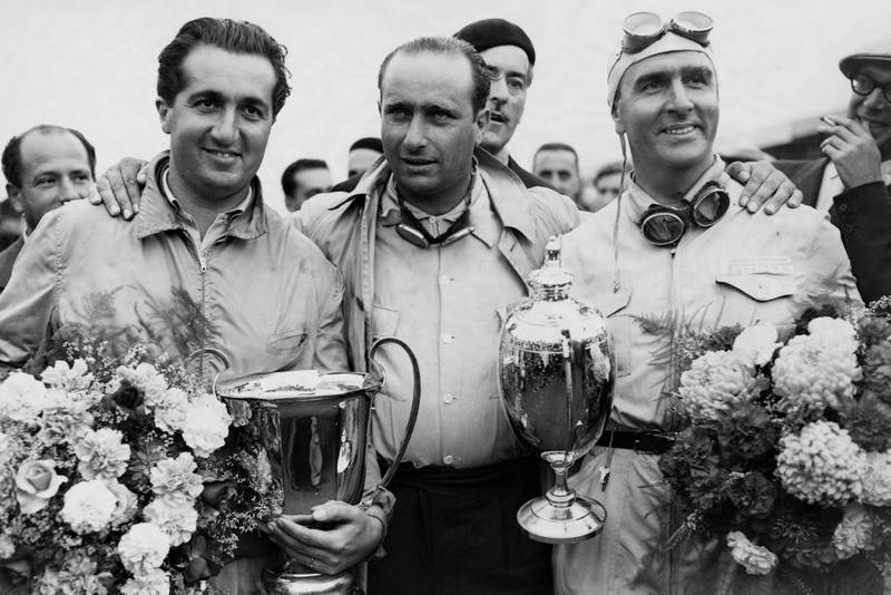 Juan Fangio stands between Alberto Ascari and Guiseppe Farina who hold their trophies and bouquets after the auto race at Silverstone.