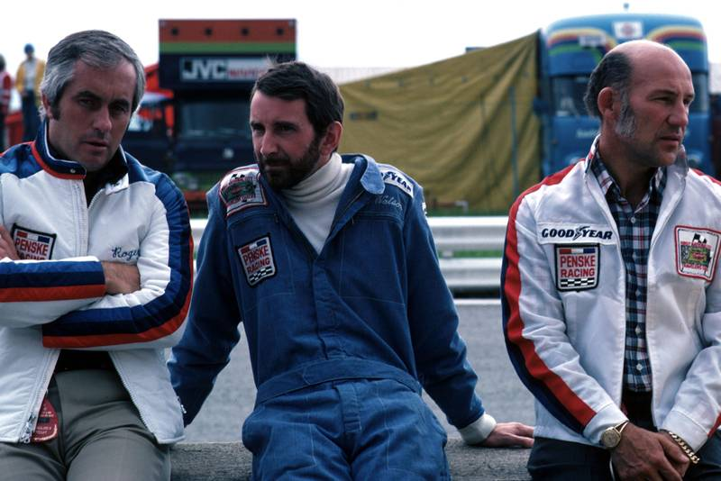John Watson (centre) sits in between Roger Penske (left) and Stirling Moss (right).