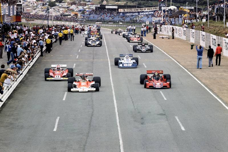James Hunt (McLaren) and Carlos Pace (Brabham) contest the lead down to the first corner at the 1977 South African Grand Prix, Kyalami.