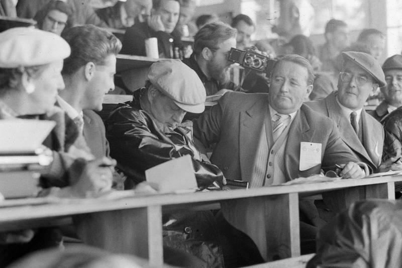 A journalist falls asleep in the press box. Denis Jenkinson can be seen checking a camera just behind.