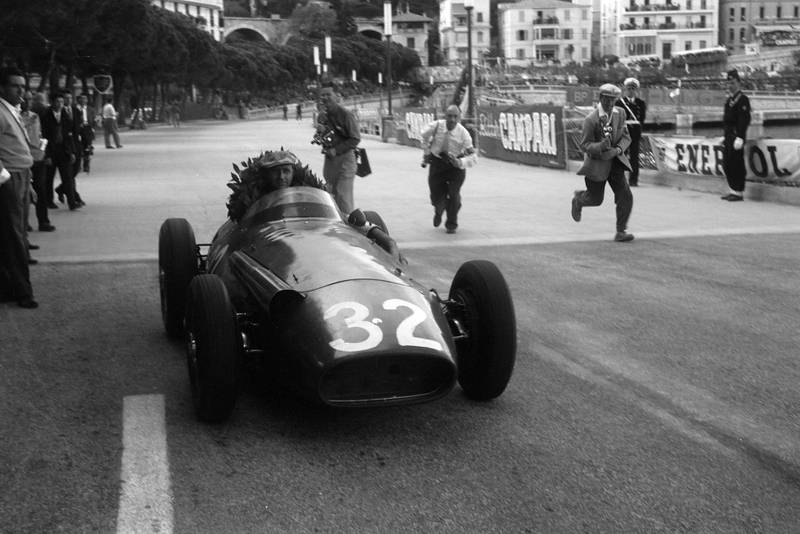 Juan Manuel Fangio has his winner's wreath propped up in the car Maserati 250F, after the race, Monaco
