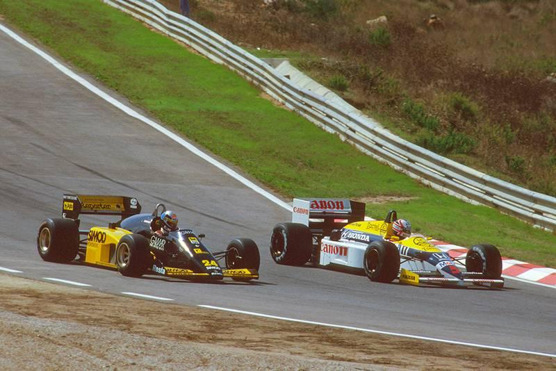 Nigel Mansell in aWilliams FW11 Honda laps Alessandro Nannini driving a Minardi M185B Motori Moderni.