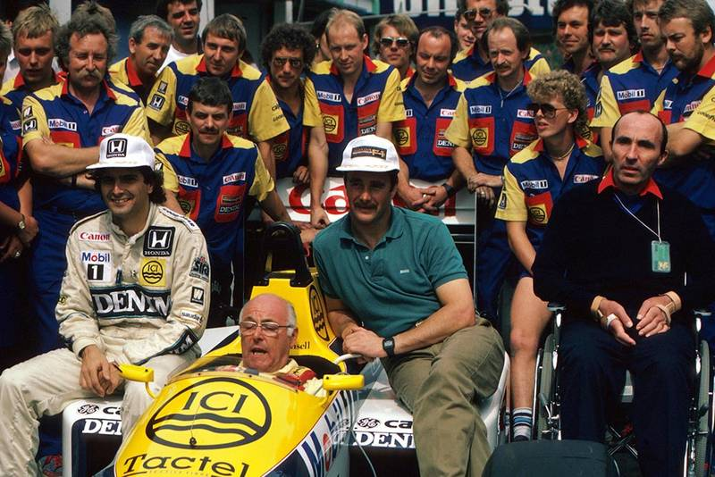 BBC TV commentator Murray Walker in the Williams FW11 sits with the regular drivers Nelson Piquet (left) and Nigel Mansell. Team Owner Frank Williams sits to the right.