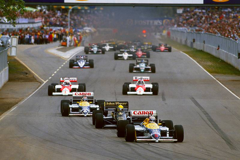 Nigel Mansell in his Williams FW11 Honda leads the field on the warm up lap.