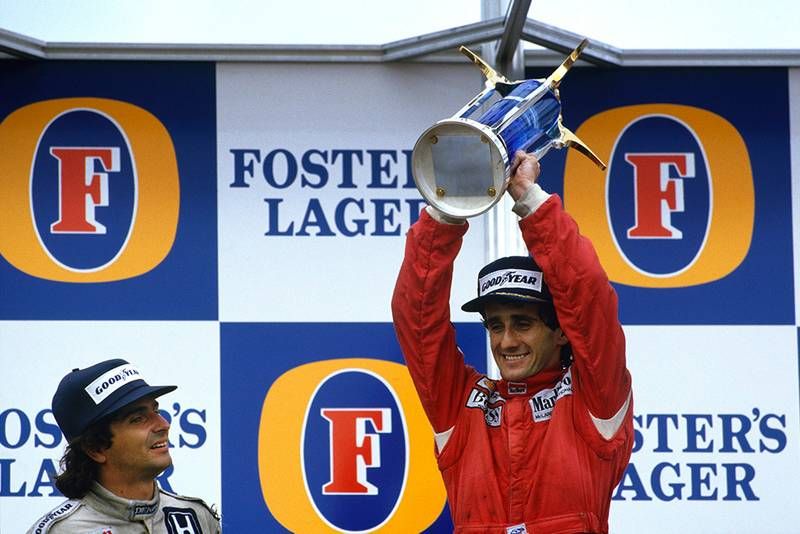 Alain Prost, 1st position, celebrates becoming World Champion again with Nelson Piquet, 2nd position, on the podium.