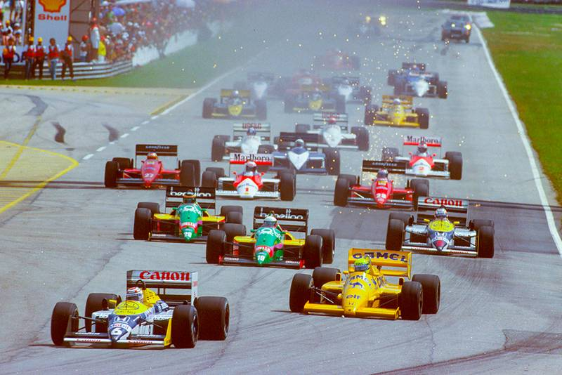 Nelson Piquet (Williams FW11B Honda) leads Ayrton Senna (Lotus 99T Honda), Teo Fabi and Thierry Boutsen (both Benetton B187 Ford's) and Nigel Mansell (Williams FW11B Honda) at the start.