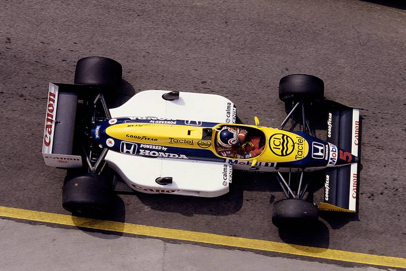 Nigel Mansell driving his Williams FW11B Honda in 1st position.