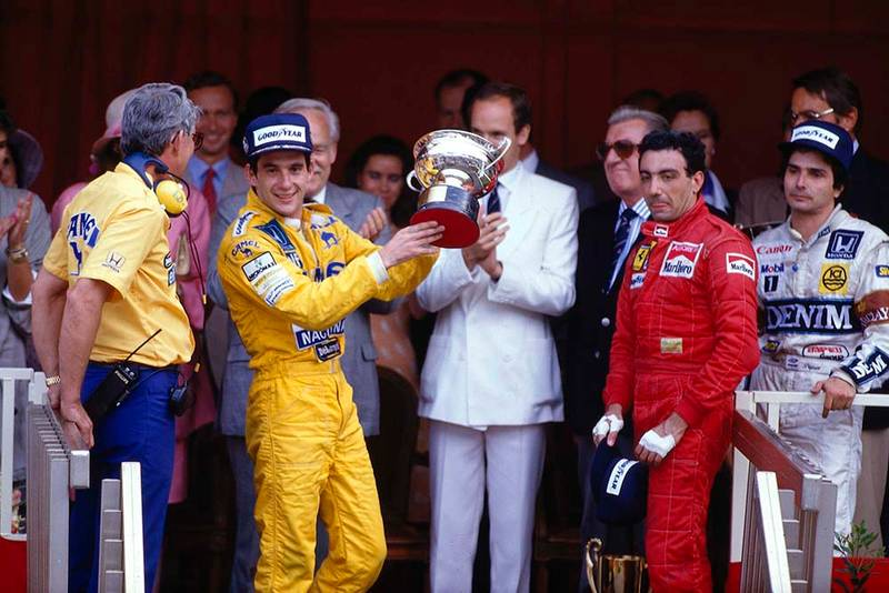 Ayrton Senna, 1st position, Michele Alboreto, 3rd position and Nelson Piquet, 2nd position on the podium. Lotus boss Peter Warr stands next to Senna to collect the constructors prize.