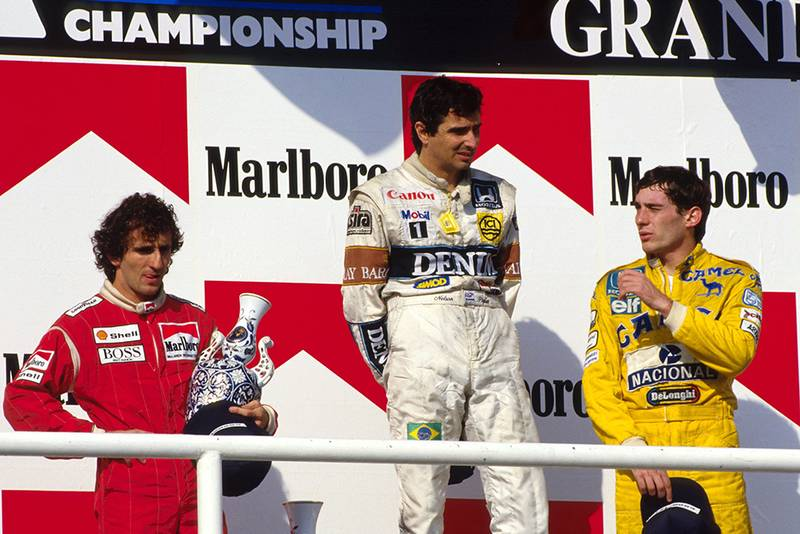 Nelson Piquet (1st) middle, Alain Prost (2nd) McLaren, left and Ayrton Senna (3rd) right on the podium.