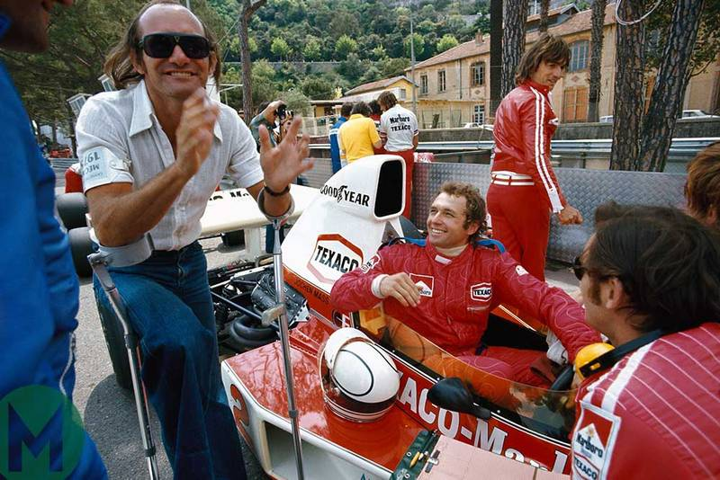 Mike Hailwood laughing with Jochen Mass in his McLaren at 1975 Monaco GP