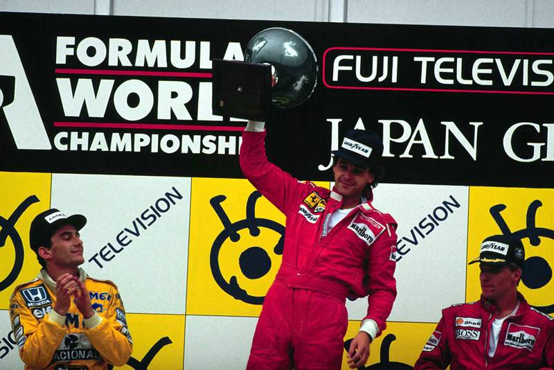 On the podium at Suzuka, Japan, Gerhard Berger, Ayrton Senna and Stefan Johansson celebrate finishing in 1st, 2nd and 3rd positions respectively.
