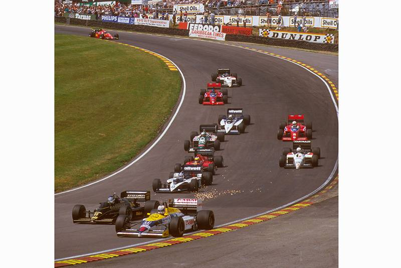 Nigel Mansell in 1st position exits Paddock Hill Bend ahead of the pack.