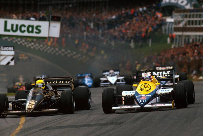 Nigel Mansell in his Williams FW10 challenges pole sitter Ayrton Senna in a Lotus 97T into Paddock Hill Bend.