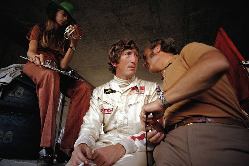 Jochen Rindt confers with Lotus team boss COlin Chapman whilst sitting next to wife Nina at the 1970 Austrian Grand Prix.