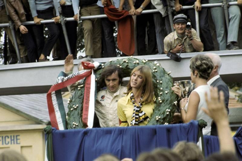 Jackie Stewart celebrates on the podium after winning the 1969 Italian Grand Prix.