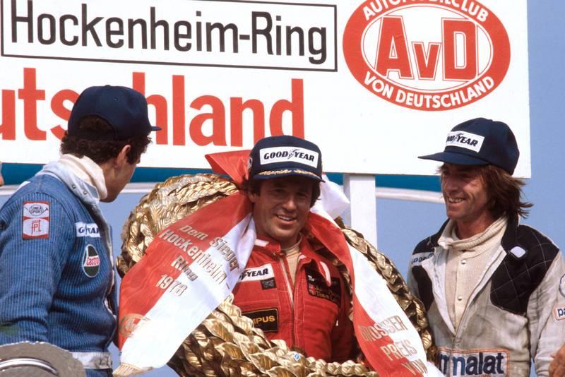 Mario Andretti (Lotus) celebrates on the podium after winning the 1978 German Grand Prix, Hockenheim.