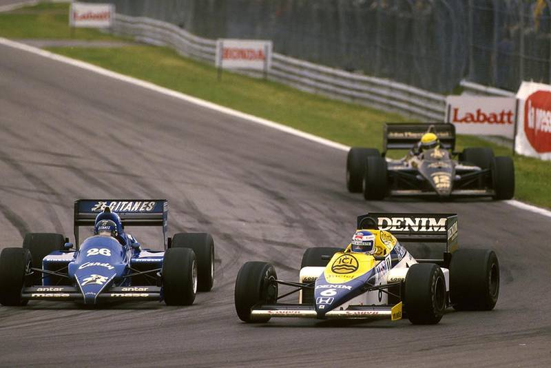 Keke Rosberg in his Williams FW10 passes Jacques Laffite in a Ligier JS25.