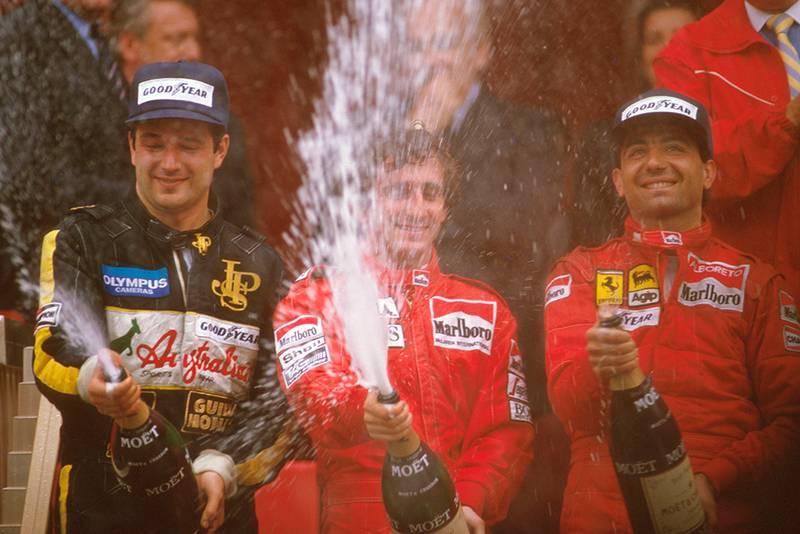 Alain Prost, 1st position, Elio de Angelis, 2nd position and Michele Alboreto, 3rd position on the podium.