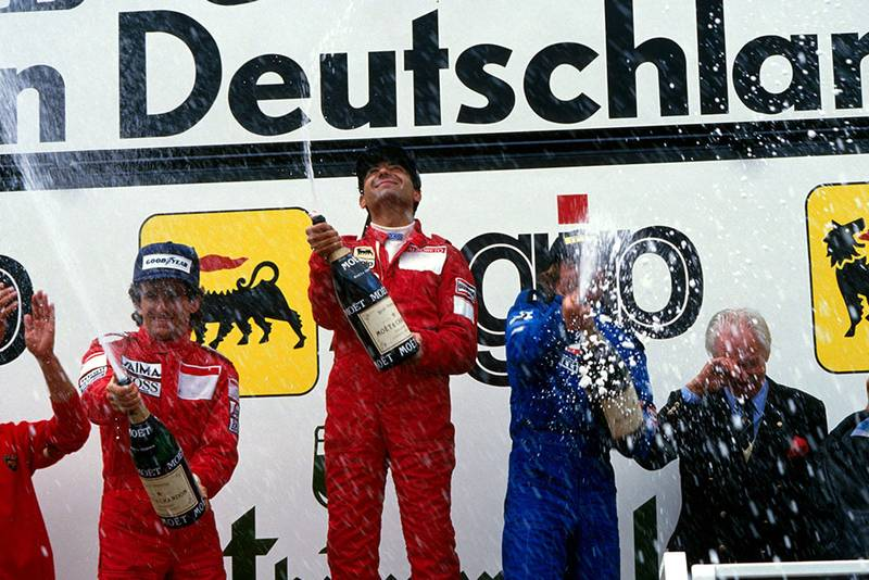 L to R: Alain Prost, 2nd, winner Michele Alboreto and Jacques Laffite, 3rd on the podium.