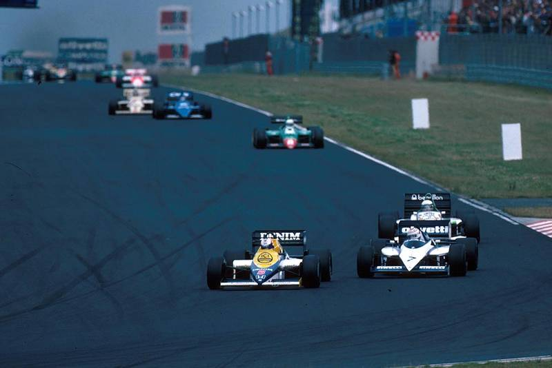 Nigel Mansell in his Williams FW10 leads the field.