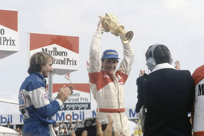 John Watson, 1st position and Jacques Laffite, 3rd position on the podium.