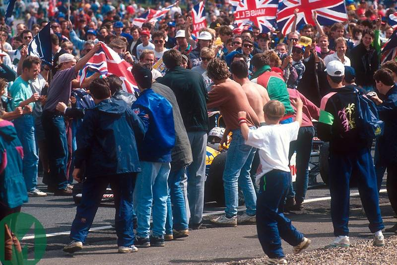 The Silverstone crowd surrounds Nigel Mansell's car on track at the 1992 British Grand Prix