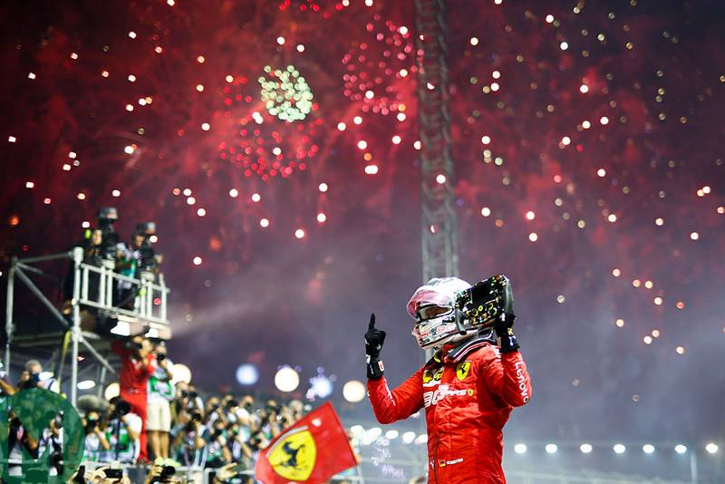 Sebastian Vettel holds his steering wheel in the air beneath fireworks after winning the 2019 Singapore Grand Prix