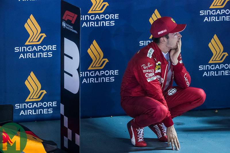 Charles Leclerc crouches in pac ferme at the end of the 2019 F1 Singapore Grand Prix