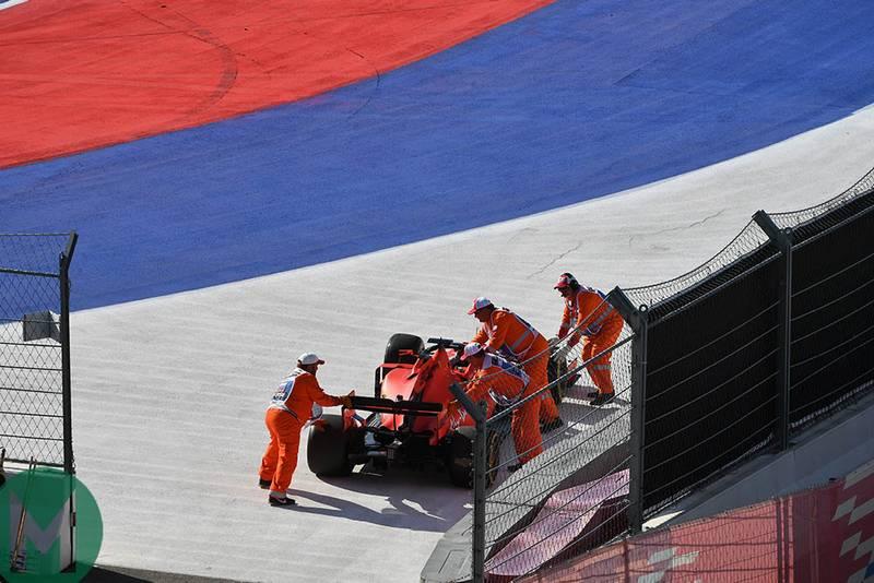 Marshals wheel Sebastian Vettel's car away after he retired from the 2019 F1 Russian Grand Prix