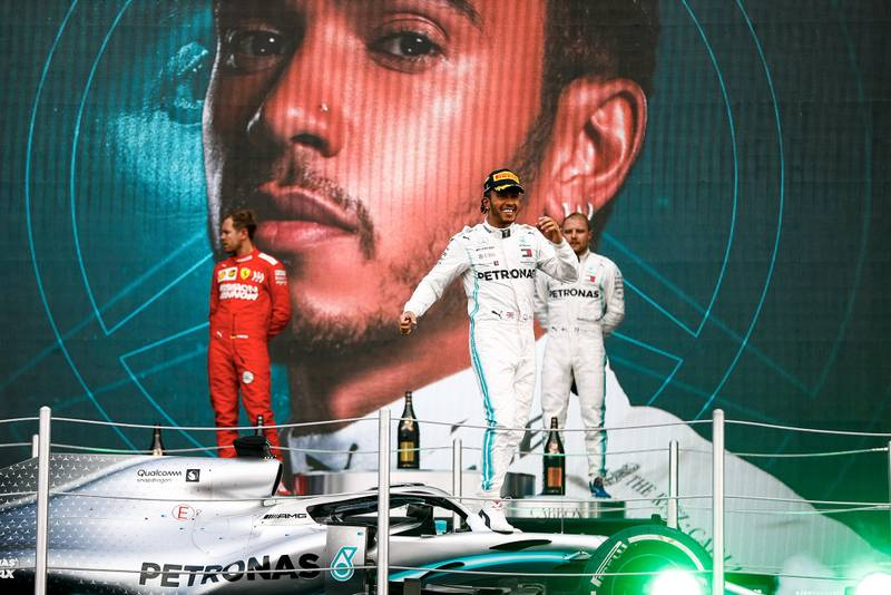 Lewis Hamilton is raised onto the podium with his car after winning the 2019 F1 Mexican Grand Prix