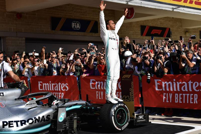 Lewis Hamilton stands on his car and raises his arms to the crowd after winning the 2019 F1 World Championship at the US GP