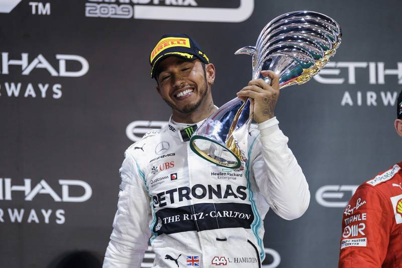Lewis Hamilton smiles with the race-winning trophy from the 2019 F1 Abu Dhabi Grand Prix