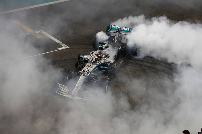 Smoke surrounds Lewis Hamilton's Mercedes as he performs donuts on the main straight in Abu Dhabi