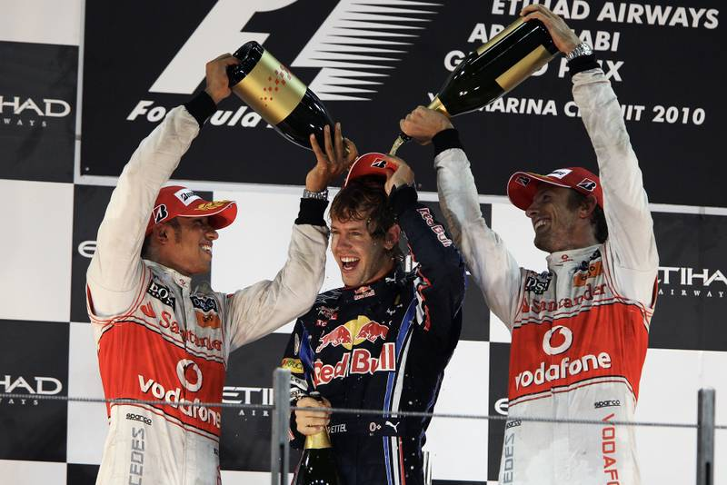 Lewis Hamilton and Jenson Button pour champagne over newly-crowned 2010 F1 champion Sebastian Vettel