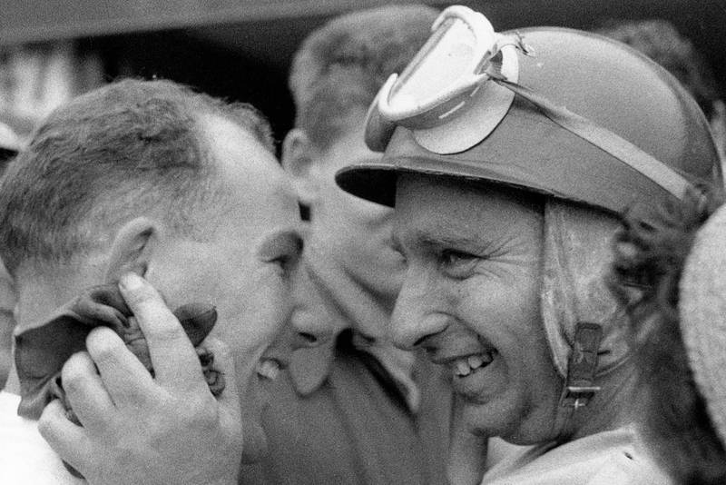 Stirling Moss and Juan Manuel Fangio share a laugh a the 1955 British Grand Prix