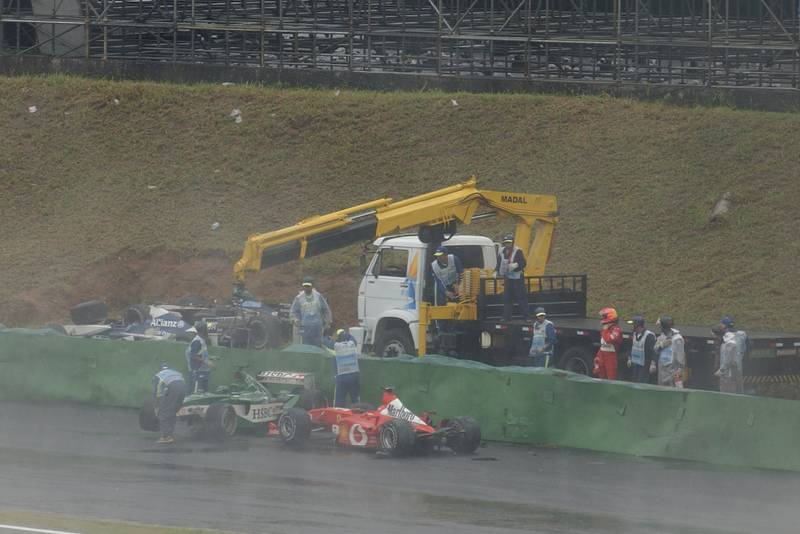 Michael Schumacher's Ferrari among the crashed cars at the trackside in the 2003 Brazilian Grand Prix