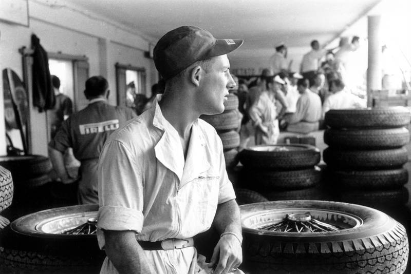 Stirling Moss surrounded by tyres in the pits at the 1954 Italian Grand Prix