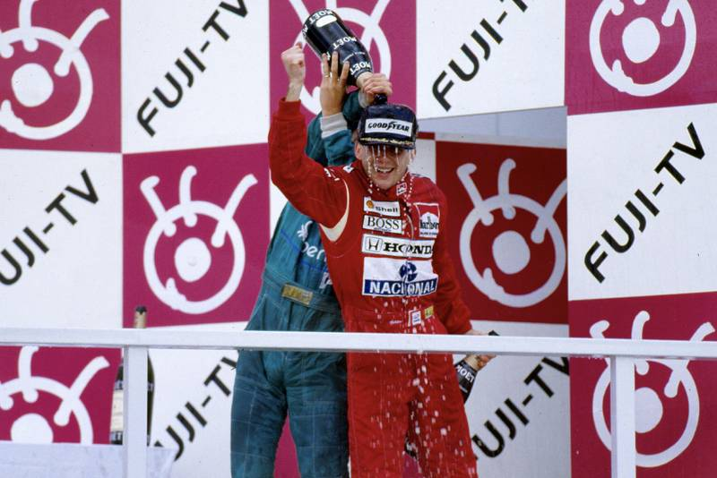 Thierry Boutsen pours champagne over Ayrton Senna on the podium at the 1988 Japanese Grand Prix