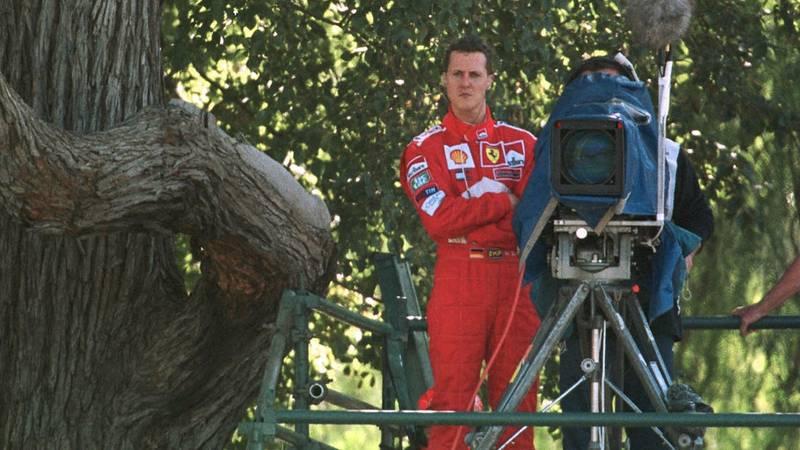 Michael Schumacher stands next to a TV camera