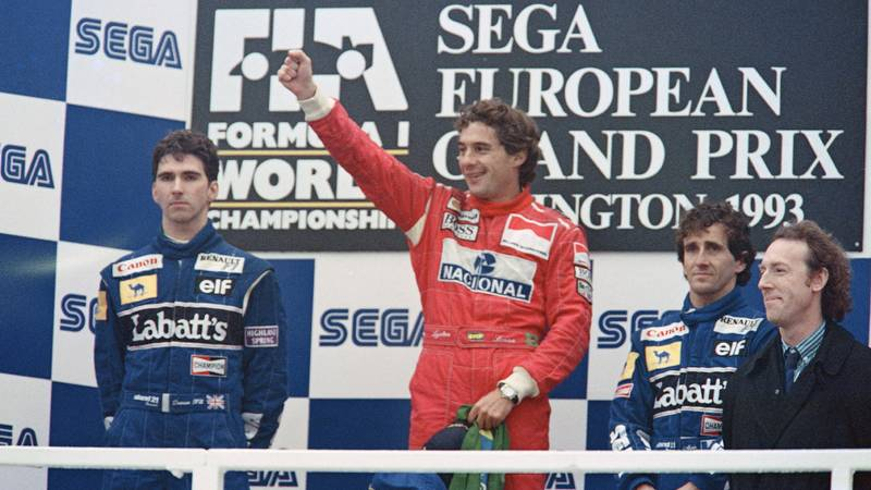 Ayrton Senna raises his arm in triumph next to Damon Hill and Alain Prost on the podium after winning the 1993 F1 European Grand Prix at Donington Park