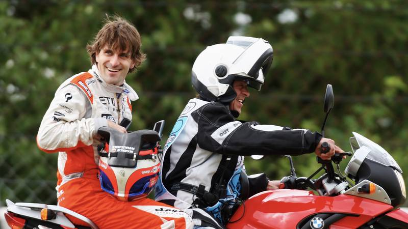 Markus Winkelhock smiles as he is drivern away after retiring from the 2007 European F1 Grand Prix at the Nurburgring
