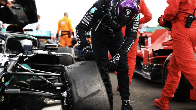 Lewis Hamilton looks at his deflated tyre after winning the 2020 f1 British Grand Prix at Silverstone