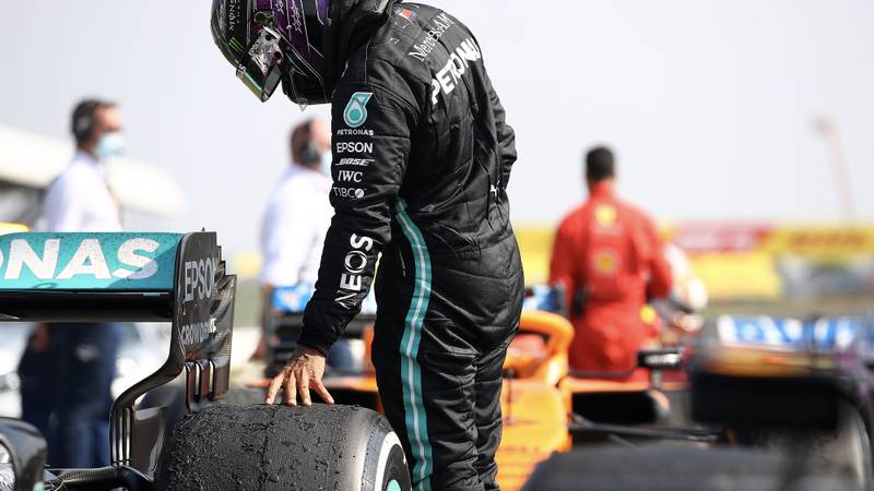 Lewis Hamilton looks at the tyre damage on Valtteri Bottas' Mercedes W11 at the end of the 2020 f1 70th Anniversary Grand Prix